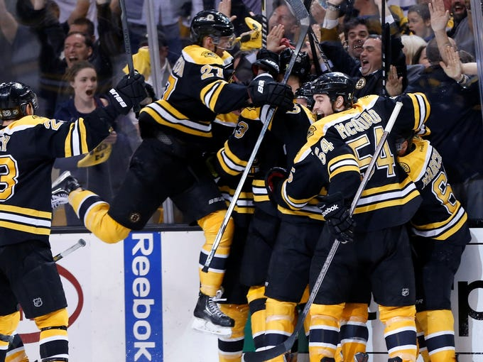 The Boston Bruins swarm around center Patrice Bergeron after he scored a goal in overtime to defeat the Toronto Maple Leafs in Game 7 at TD Garden.