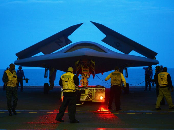 An X-47B Unmanned Combat Air System demonstrator aircraft is towed into the hangar bay of the U.S. Navy aircraft carrier USS George H.W. Bush on May 13. The carrier catapult-launched the unmanned aircraft from its flight deck May 14.