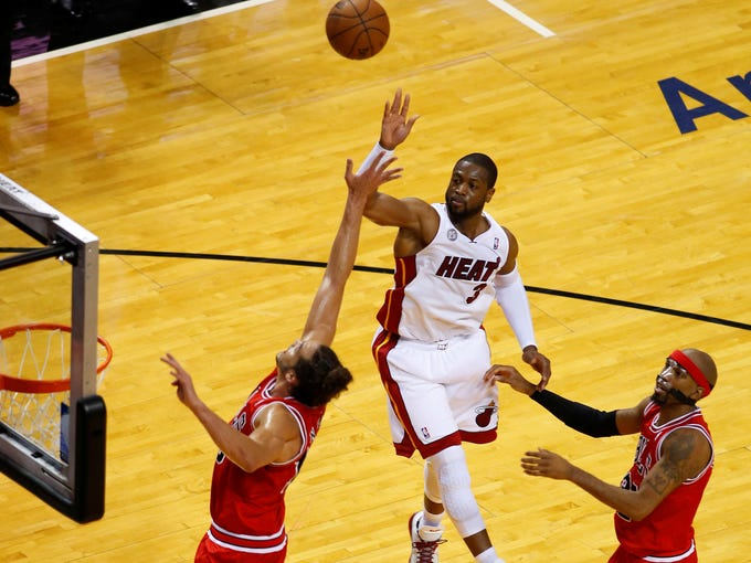 Game 5 in Miami: Heat 94, Bulls 91 -- Dwyane Wade (3) takes a shot over Joakim Noah (13) and Richard Hamilton (32).
