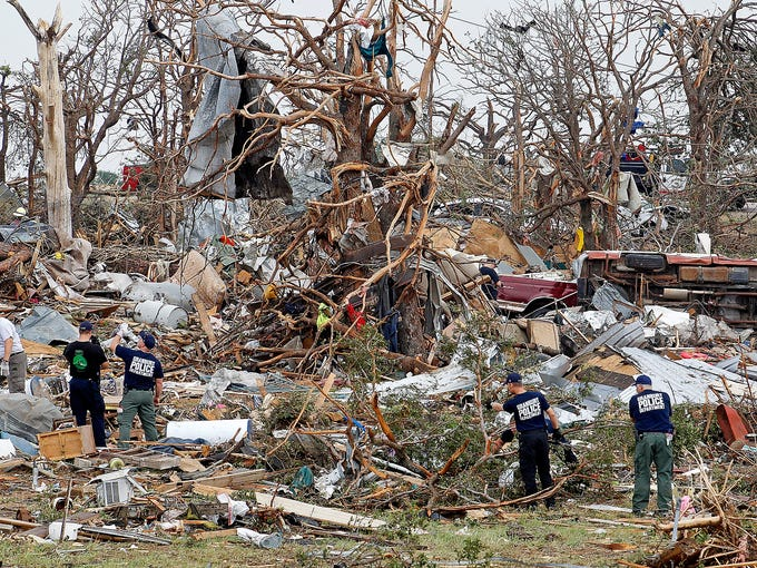 Rescue workers search through a pile of crushed cars and destroyed homes after a tornado on May 16 in the Rancho Brazos neighborhood in Granbury, Texas.