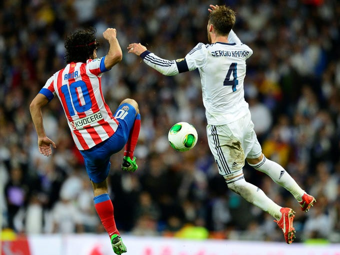 Real Madriddefender Sergio Ramos, right, vies with Atletico Madrid midfielder Arda Turan during the Copa del Rey final.