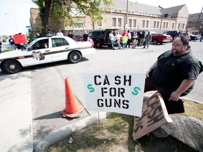 """Residents offering cash for guns wait near the location of a """"Groceries For Guns"""" gun buyback program May 18 at the New St. Paul Tabernacle Church of God in Christ in Detroit."""