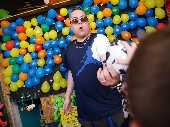 Jason Villano awards a stuffed animal to a winner at his boardwalk balloon-pop amusement game on May 12 in Seaside Heights, N.J.