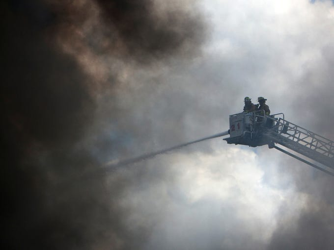 Firefighters battle a fire at the Southwest Inn, Friday, in Houston.A fire that engulfed a Houston motel has injured at least six firefighters, including two critically, and three people are missing.