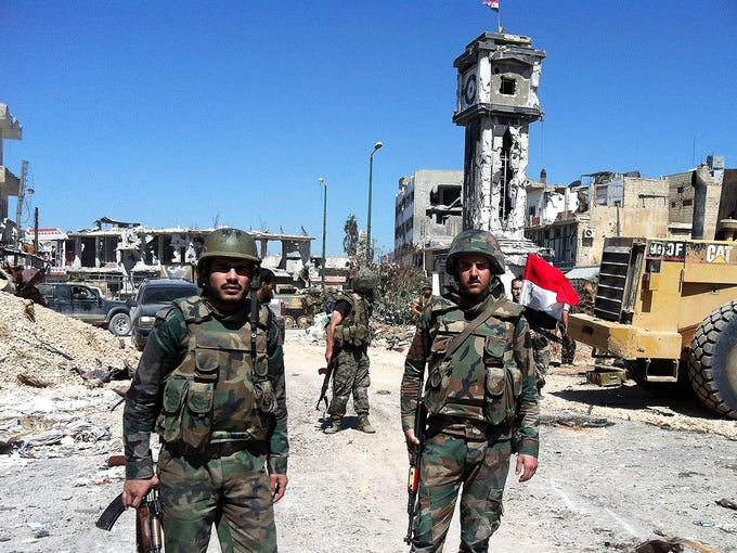 Syrian government soldiers stand in the main square of al-Qusayr on June 5 after capturing the town from rebel forces. The town was the rebels' principal transit point for weapons and fighters from neighboring Lebanon.
