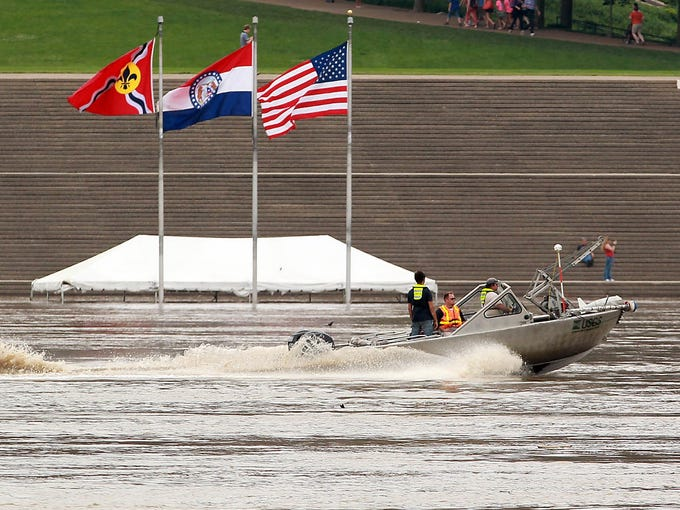 A boat motors down the riverfront near the steps to the Gateway Arch on June 4 in St. Louis, Mo. The Mississippi River crested at 40.52 feet in St. Louis.