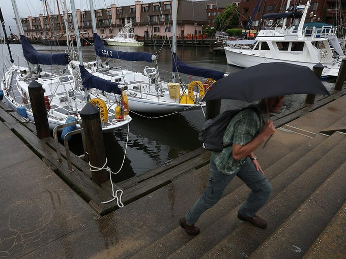 John Ulvestad, a member of the U.S. Navy Patuxent Sailing Club, leaves the waterfront as rain from Tropical Storm Andrea falls on June 7 in Norfolk, Va. An annual sailing event in Norfolk was been canceled due to bad weather from the storm.