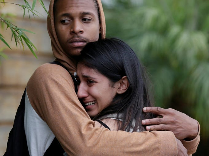 A weeping woman is comforted after being escorted off campus as Police swarm Santa Monica City College.