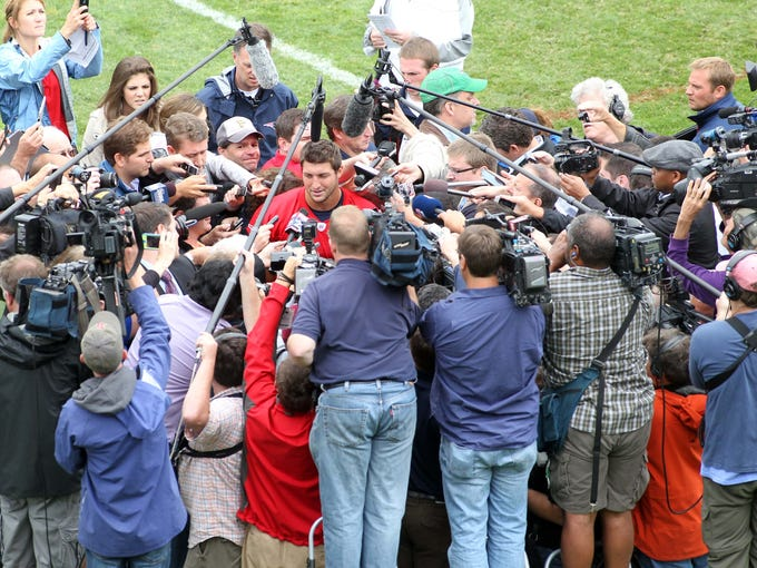 Members of the media greet New England Patriots quarterback Tim Tebow after practice during the team's minicamp at Gillette Stadium.