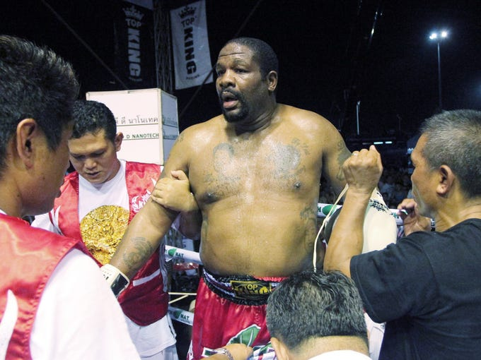 Former heavyweight boxing champion Riddick Bowe is treated by corner men after he was knocked down by Levgen Golovin during their World Muay Thai fight in Pattaya, Thailand. Golovin won the bout in a second-round knockout by kicking on the leg.