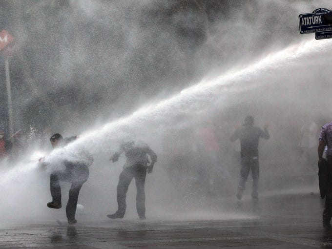 Turkish riot police spray water at demonstrators near Kizilay Square in Ankara, Turkey, on June 16.