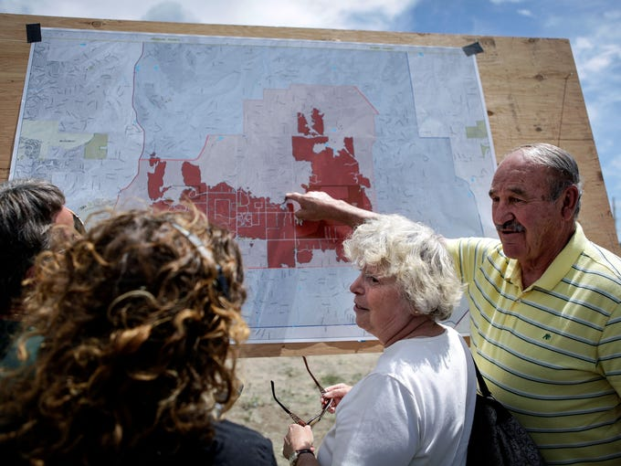 Ron Pedron, right, and his wife, Rita, talk to residents about a fire and evacuation map before a news conference June 16 at Pikes Peak Community College's Rampart Range campus near Colorado Springs.  Nearly 500 homes have been burned by the Black Forest Fire.