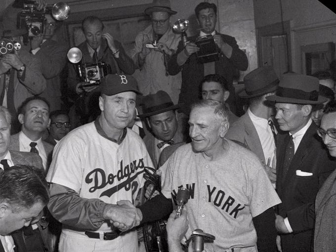 Brooklyn Dodgers manager Walter Alston, left, congratulates New York Yankees manager Casey Stengel in the Yankees' dressing room after the Yankees beat the Dodgers in Game 7 to win the World Series on Oct. 10, 1956, at Ebbets Field.