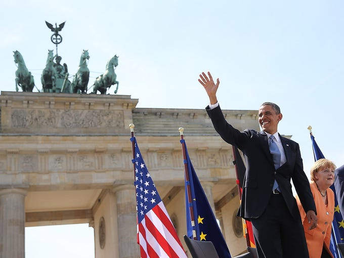 President Obama waves as he arrives at the Brandenburg Gate with German Chancellor Angela Merkel at Pariser Platz on June 19 in Berlin.