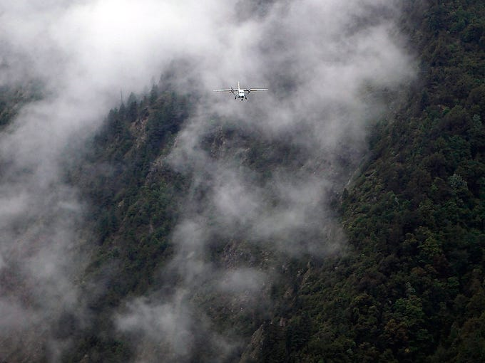 A flight approaches Lukla airport for a landing on May 28. If the pilot misses the runway, the plane will slam into a mountain.
