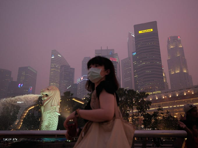 A woman wears a mask to protect herself from severe air pollution on June 20 in Singapore. Wind has driven smoke from huge forest fires in neighboring Indonesia into the city, forcing many people to remain indoors to avoid unprecedented levels of air pollution.