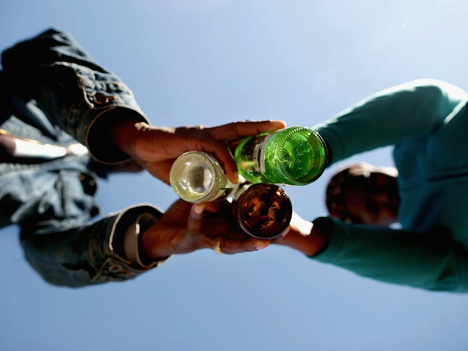 Pastor Maxwell Ncube, left, of the Indumiso Yamakholwa In Zion Church blesses bottles containing water and written prayers during a ceremony in the Yeoville neighborhood June 21 in Johannesburg. After the ceremony the bottles will be smashed to release the prayers to God.