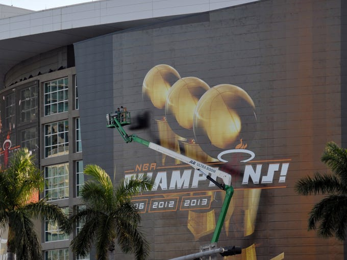 Workers on a boom prepare American Airlines Arena for the Miami Heat's celebration of their NBA title won after beating the San Antonio Spurs in seven games.