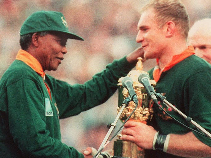 South African rugby team captain Francois Pienaar is congratulated by Mandela after South Africa won the 1995 Rugby World Cup final against New Zealand  in Johannesburg.