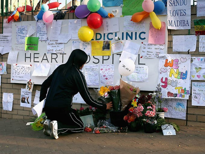 A woman places flowers at the base of the wall decorated with messages of support for former South African President Nelson Mandela outside the Mediclinic Heart Hospital on June 25 in Pretoria, South Africa. Mandela, 94, has been hospitalized since June 8 for what the government says is a recurring lung infection.