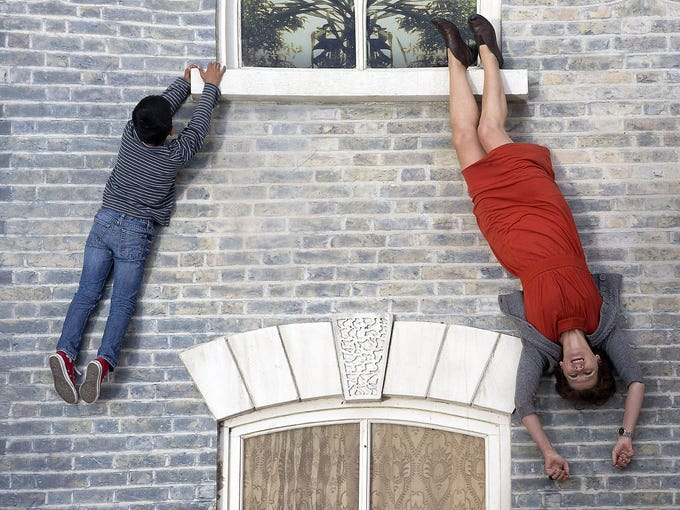 "People play on a large installation piece by Argentinian artist Leandro Erlich titled ""Dalston House"" on June 25 in East London. The piece is a replica of a 19th-century Victorian home lying on the ground. A large mirror is angled above it, giving the illusion of people hanging from the home."