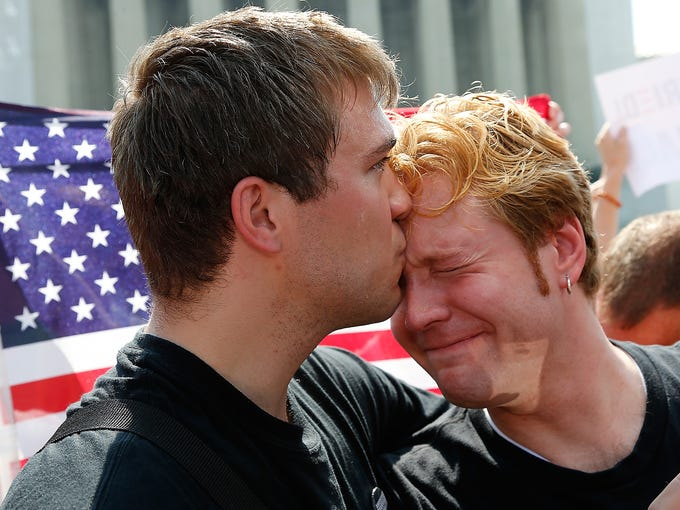 Michael Knaapen, left, and his husband, John Becker, embrace after the Supreme Court struck down a federal provision denying benefits to legally married gay couples in front of the Supreme Court on June 26 in Washington, D.C.