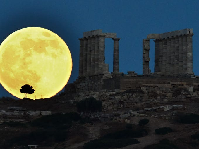 A supermoon rises next to the ancient Greek temple of Poseidon at Cape Sounion, some 65 kilometers south of Athens, on June 23.