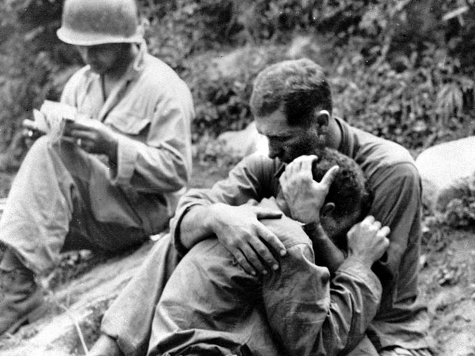 An American infantryman, his buddy killed in action in the Korean War, weeps on the shoulder of another GI in Korea Aug. 28, 1950. A corpsman, left, goes about the business of filling out casualty tags.