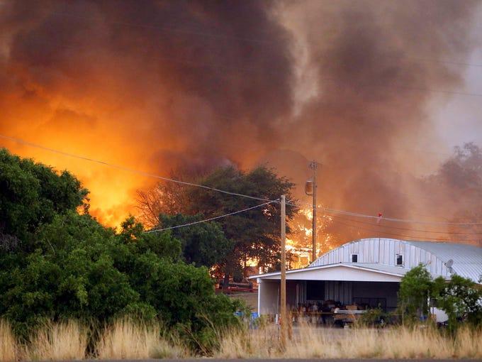 Homes burn as a fire approaches Glenn Ilah on June 30 in Yarnell, Ariz.