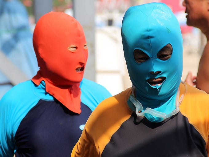 People wear a protective head masks dubbed the face-kini on July 3 on a beach in Qingdao, China. Many people in China do not want a tan, especially on the face.