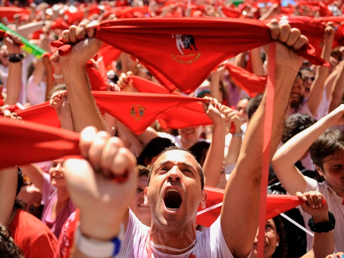 Revelers hold up traditional red neckties in the main square of Pamplona, Spain, to celebrate the start of the San Fermin Festivalon July 6, 2013.The event is a combination of three historic festivals: a livestock fair and exhibition; the San Fermin