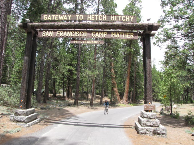 USA TODAY's Elizabeth Weise rides her bike through the entrance sign to Camp Mather, one hour northwest of Yosemite National Park.