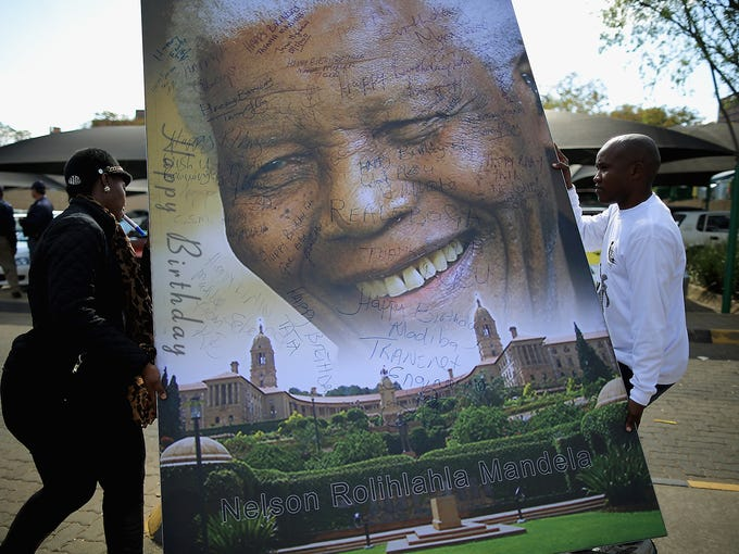 Workers carry a portrait of Nelson Mandela as thousands of people celebrate his 95th birthday outside the Mediclinic Heart Hospital on July 18 in Pretoria, South Africa. Mandela has been in the hospital since June 8 for treatment for a recurring lung infection.