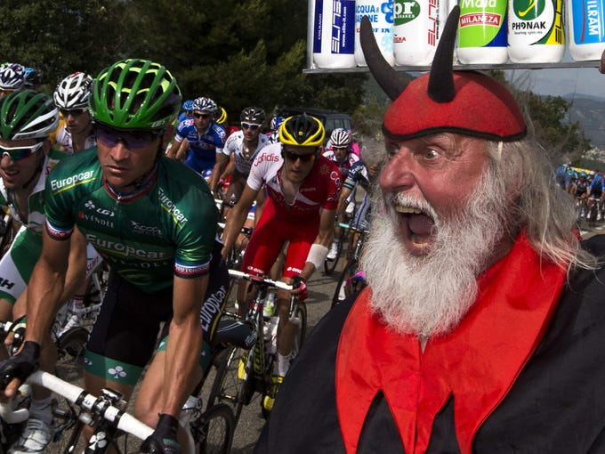 """""""El diablo"""" cheers riders during the 228.5 km fifth stage of the 100th edition of the Tour de France."""