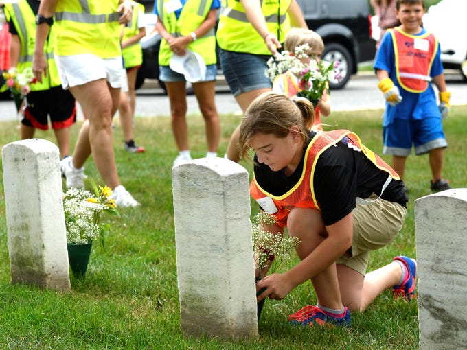 Alyssa Moody, 9, of Maine places flowers at one of the oldest graves at Arlington National Cemetery during the 17th Annual Renewal and  Remembrance beautification project.