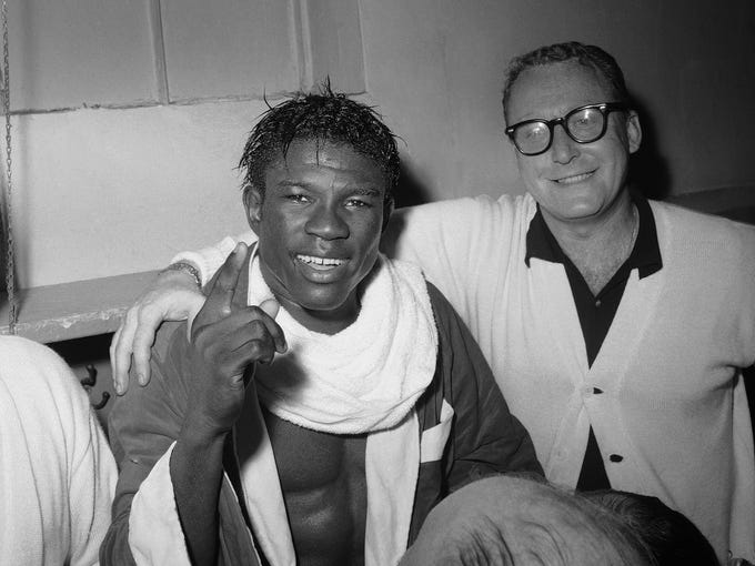 Emile Griffith smiles after regaining his welterweight world championship title by defeating Luis Rodriguez in 1963. At right is Griffith's coach Gil Clancy. The International Boxing Hall of Fame says former world champion boxer Emile Griffith has died. He was 75.