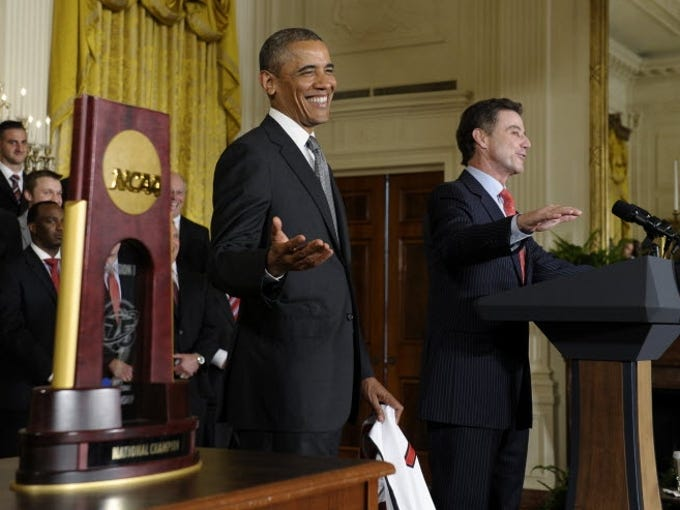 With the championship trophy sitting at left, President Barack Obama laughs as Louisville men's basketball coach Rick Pitino, right, says he was disappointed that he didn't meet first lady Michelle Obama
