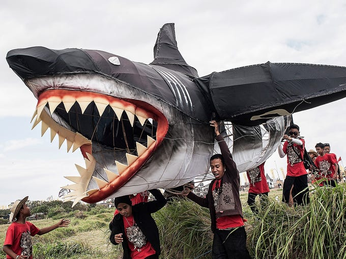 People carry a shark-shaped kite at the Bali Kite Festival on July 26 in Denpasar, Indonesia. The event is a seasonal religious festival intended to send a message to Hindu Gods to create abundant harvests and crops.