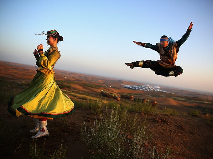 Dancers in traditional costumes perform near Desert Lotus Hotel in Xiangshawan Desert on July 19 in Ordos, Inner Mongolia Autonomous Region, China. The resort is located in the middle of the Kubuqi Desert near Ordos City.