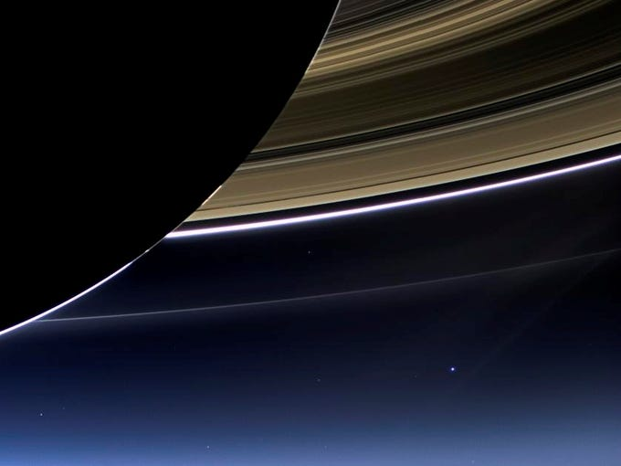 This July 19 image from the Cassini spacecraft provided NASA shows the planet Earth, bright dot at center right, below Saturn's rings.