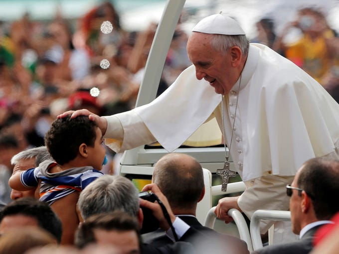 Pope Francis blesses a child as he rides in the popemobile to celebrate Mass in Rio de Janeiro on July 28. Hundreds of thousands of young people slept under chilly skies in the white sand of Copacabana beach awaiting the pope's final Mass for World Youth Day.