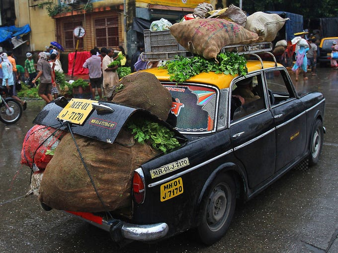 A  Premier Padmini taxi is overloaded with vegetables as it drives along a street on Aug. 2 in Mumbai, India. About 4,500 of these taxis will be banned from the roads since the government enacted a law banning cabs over 20 years old.