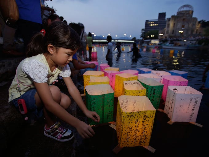 A girl releases a paper lantern representing the soul of her great grandmother who died in an atomic bombing during World War II at the Motoyasu River on Aug. 6 in Hiroshima, Japan. The nation marked the 68th anniversary of the atomic bombing of Hiroshima with a ceremony to honor the dead and pledges to seek an elimination of nuclear weapons.