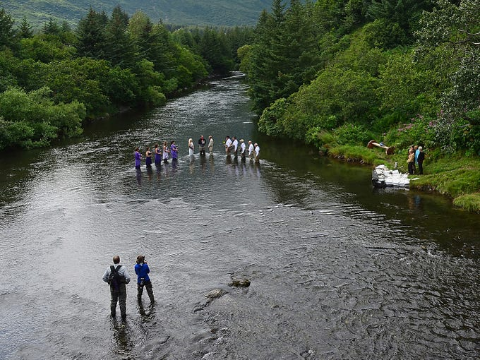 Accompanied by their wedding party, fishing guides Kadie Walsh and Dake Schmidt exchange vows in the middle of the Buskin River on Aug. 3 In Kodiak, Alaska. The fishing-themed ceremony included rings carried in the mouths of king salmon, a wedding party carrying fly fishing rods and the couple catching a pair of pink salmon together.