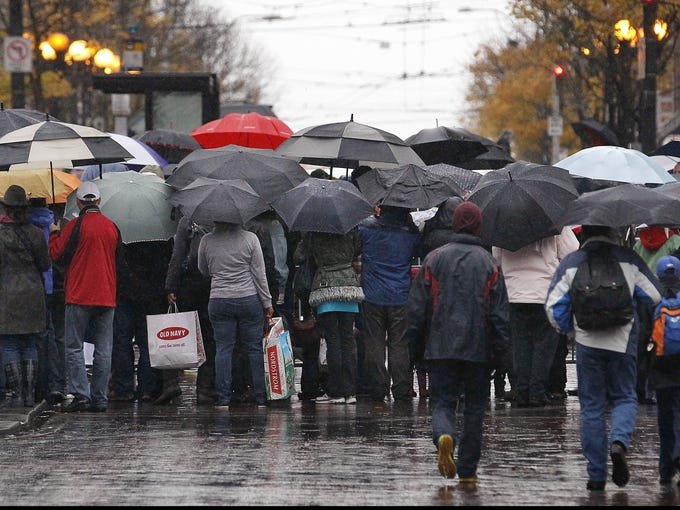 Viewers huddle under umbrellas in a heavy rain in downtown Seattle as they watch their annual Macy's Holiday Parade.