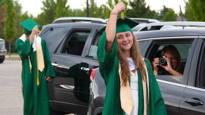 A Zeeland West High School graduate moves her tassel from right to left at the school's drive-in graduation on Friday, July 31, 2020.