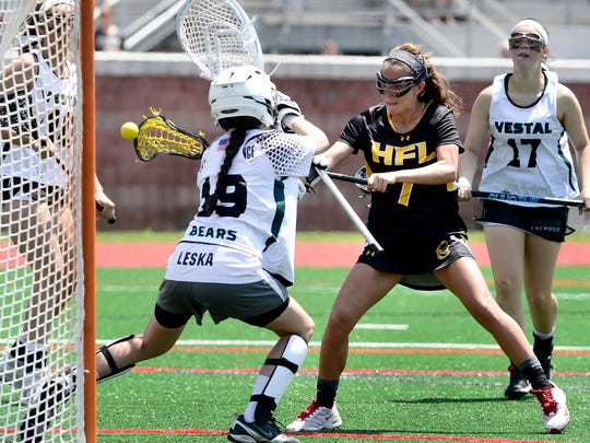 Senior Brittany Chamberlain, right, puts a shot past Vestal goalie Nicole Leska for the Cougars' fifth goal during Friday's comeback win in overtime, 8-7, at the State University of New York at Cortland on Friday.