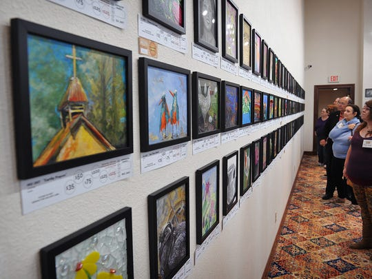 Patrons and visitors check out the opening of the Mystery Art Fest exhibit Thursday evening at the Kemp Center for the Arts. The exhibit includes more than 320 pieces of 8-by-10-inch art.
