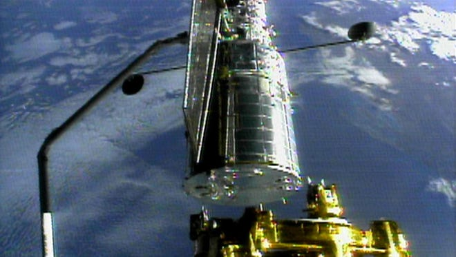 The Hubble space telescope is held by space shuttle Discovery's robot arm on Dec. 25, 1999 in preparation for its release from the shuttle. Discovery's seven person international crew redeployed the telescope after three days of repairs on this mission.