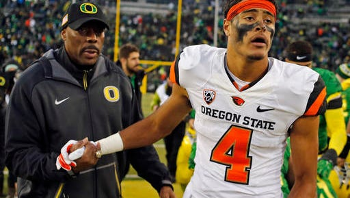 In this Nov. 27, 2015, file photo, Oregon State's Seth Collins, right, shakes hands with Oregon defensive coordinator Don Pellum after an NCAA college football game in Eugene. Heading into the final two games of the season, Oregon State was dealt another blow when receiver Collins, one of the most dynamic players on the team, was hospitalized with an undisclosed illness.